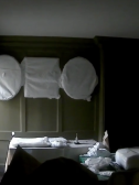 Screenshot from Virtual Edinburgh Tour showcasing a Gladstone's Land room in the stages of instalment, with objects cloth-covered to protect from dust.