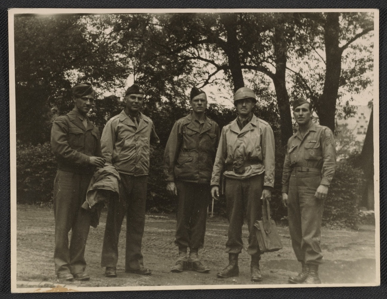 """George Stout during WWII, pictured 4th from the left. Inscription on back of photo: """"These characters, left to right are: Pfc Rowland (my driver), Capt. Hancock, Lt. Moore, old Pop, Cpt. Fontana (another driver). Picture made in Marburg, Germany, early this month, June 1945"""" (George Leslie Stout papers, 1897-1978. Archives of American Art, Smithsonian Institution.)"""