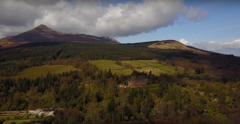 drone shot of broderick castle surrounded by trees and countryside on the isle of arran