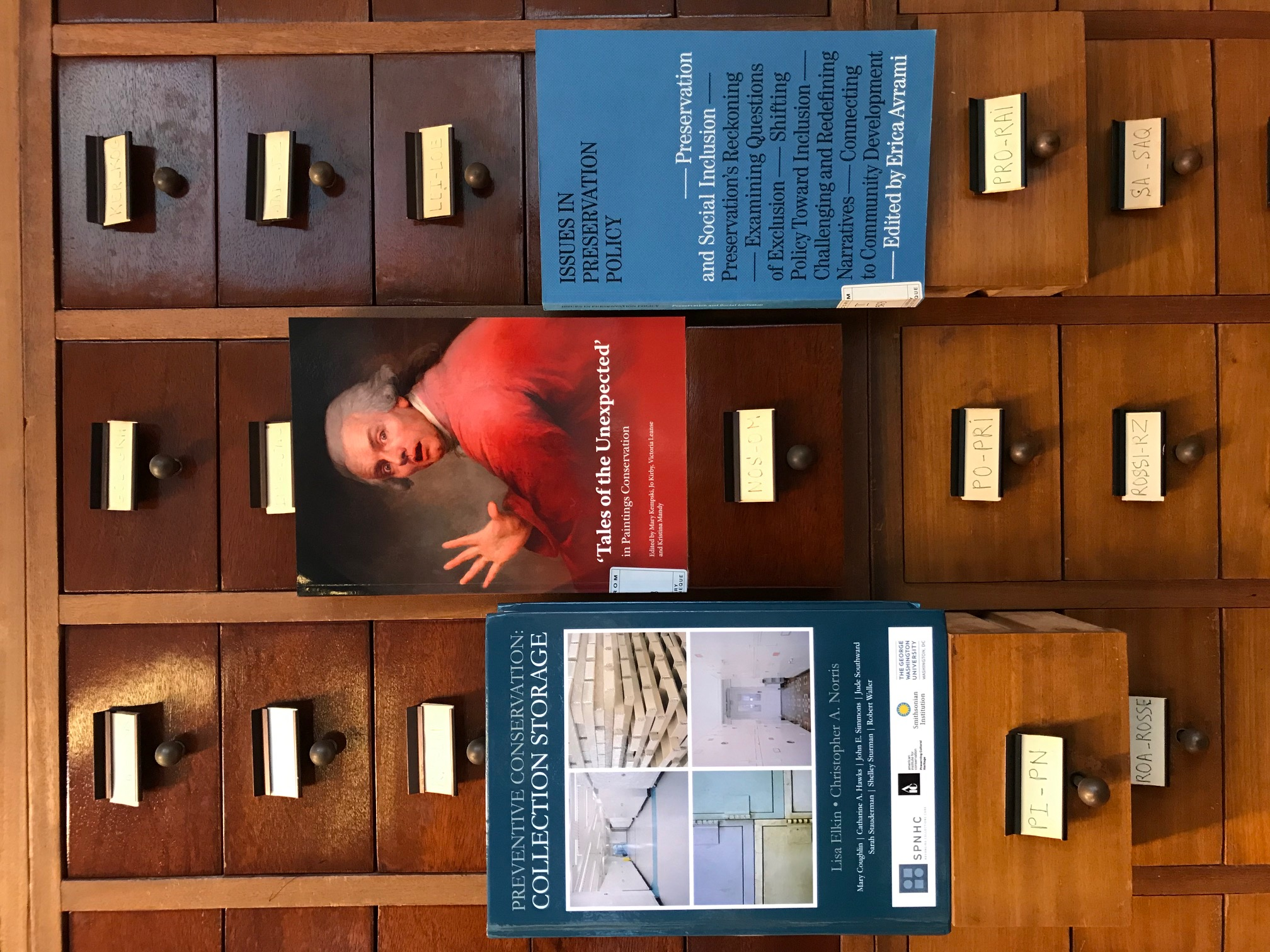 "Book covers for ""Preventive Conservation Collection Storage"", ""Tales of the Unexpected"" and ""Issues in Preservation Policy"" on the ICCROM Library card catalogue drawers. Image by Daniela Sauer."