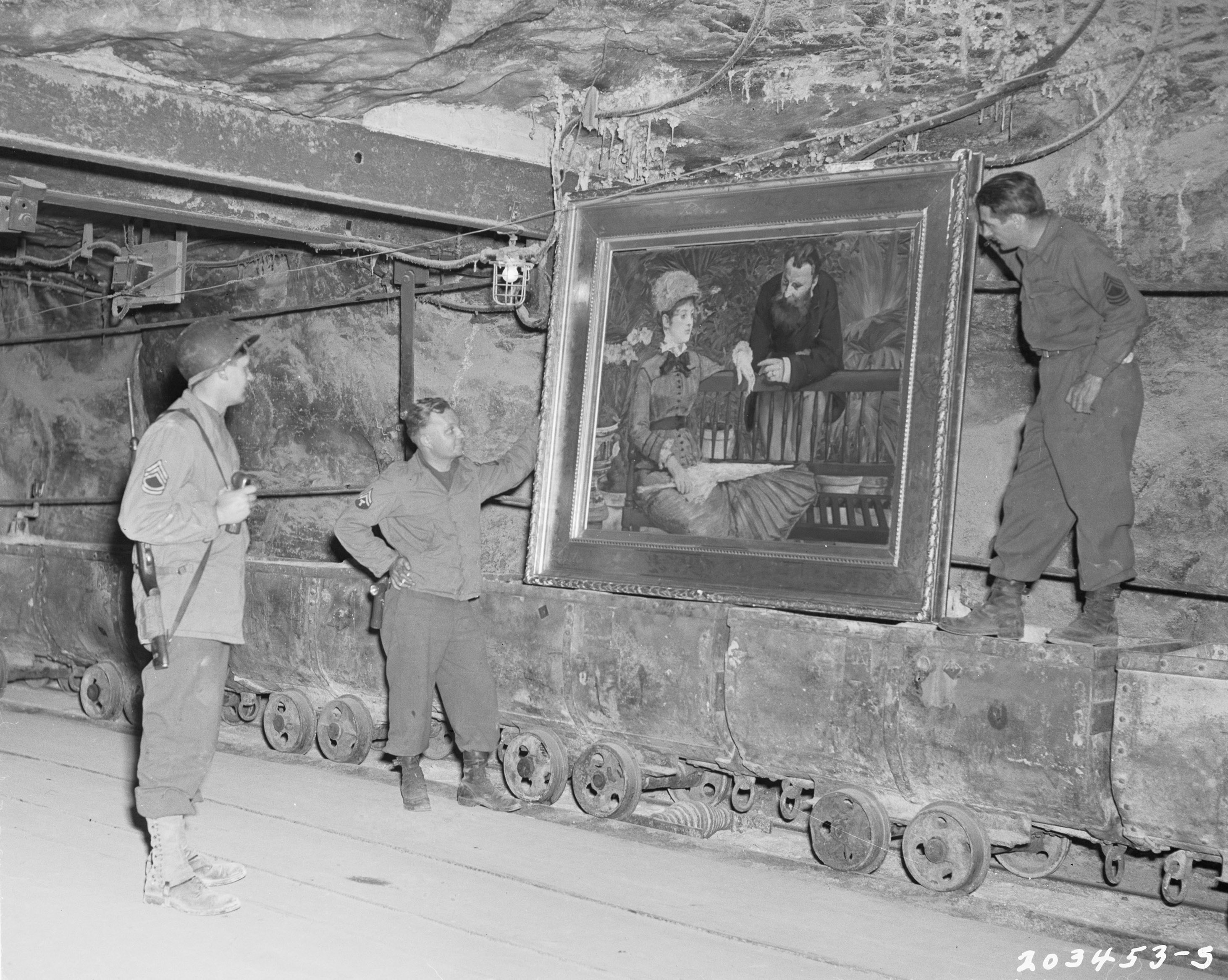 American GIs, including Sgt. Henry Hartung to the left of the painting, admire a masterpiece by Edourard Manet, stored in Merkers salt mine during WWII. This painting from Kaiser-Friderich Museum in Berlin, had been brought to the mine for safekeeping. (Photo credit: National Archives and Records Administration, College Park, MD / Public Domain)