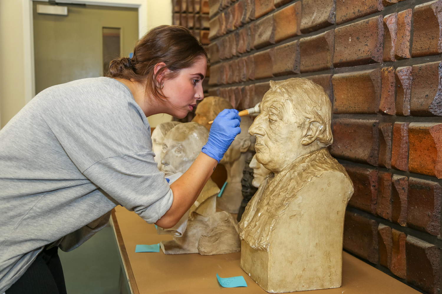 Conservator Charlotte Hanmore cleans sculptures at the Beecroft Gallery © the artist's estate. Photo, Art UK alt