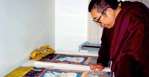 A Buddhist teacher looking at the two thangkas, still in their original textile mountings, in my studio, 1995. ©Ann Shaftel