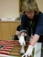 Gently vacuuming of a flag using protective netting during a textile conservation workshop held in the Naval Historical Center, Washington