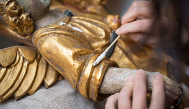 conservator hands with gold angel